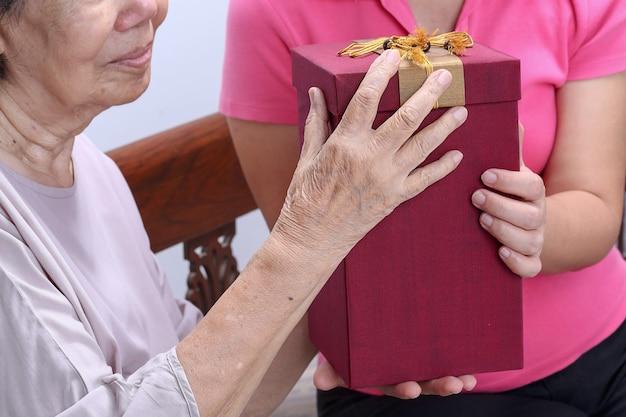 Пожилая женщина получает подарок от дочери
