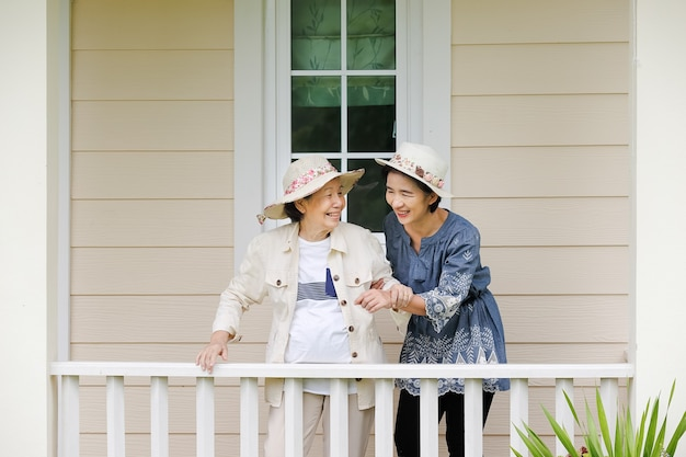 Elderly woman relax in backyard with daughter