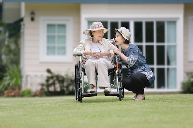 年配の女性は娘と裏庭で車椅子でリラックス