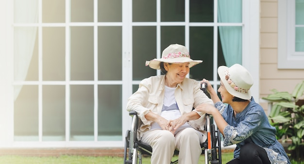 高齢者の女性は娘と一緒に裏庭で車椅子でリラックスします。