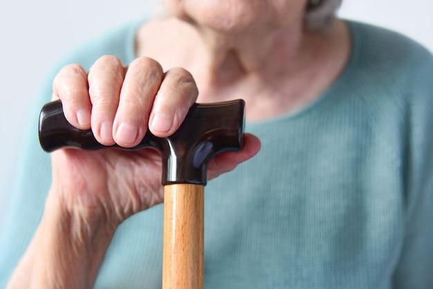 Рука пожилой женщины на ручке крупного плана деревянной трости.