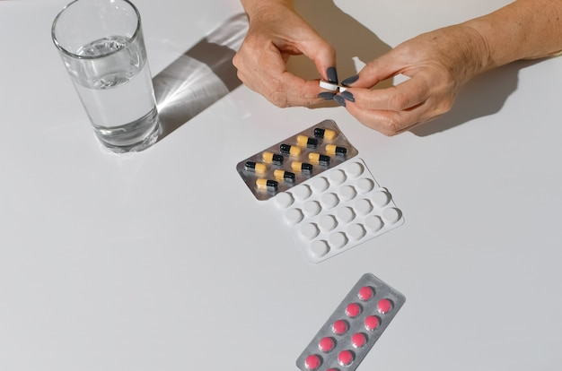 Руки пожилой женщины открывая пакет лекарств. таблетки и стакан воды на белом столе, вид сверху.