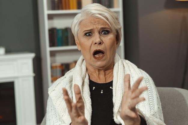 Пожилая женщина кричит от гнева и возмущения