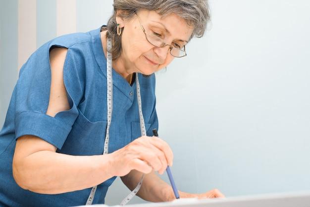 Пожилая женщина-швея, проектирующая одежду в помещении