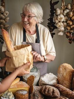 Пожилая женщина продает хлеб в гастроном