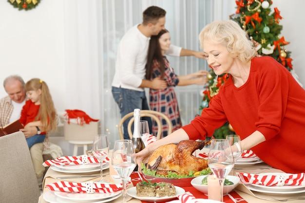 クリスマスディナーのテーブルを提供する年配の女性