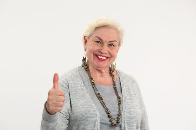 Пожилая женщина показывает палец вверх. улыбающаяся дама на белом фоне. позитивный настрой ведет к успеху.