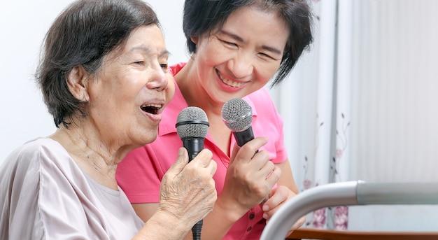 Пожилая женщина поет песню с дочерью дома.