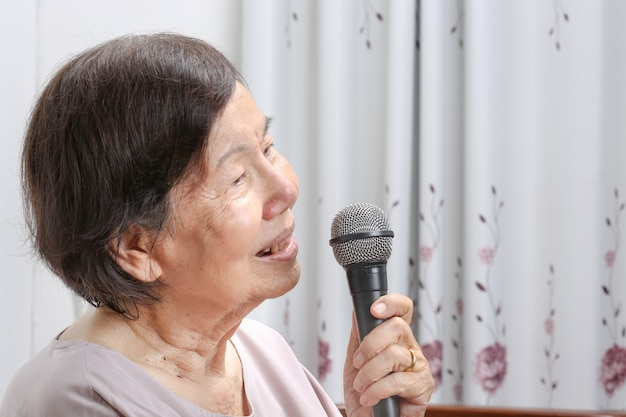 Elderly woman sing a song on microphone at home.