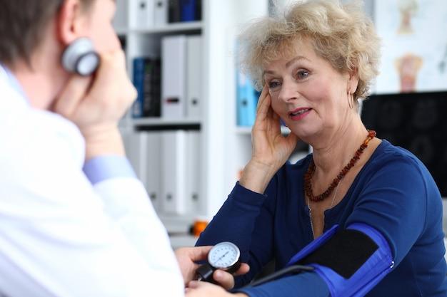 Пожилая женщина сидит на приеме у врача и жалуется на головную боль.