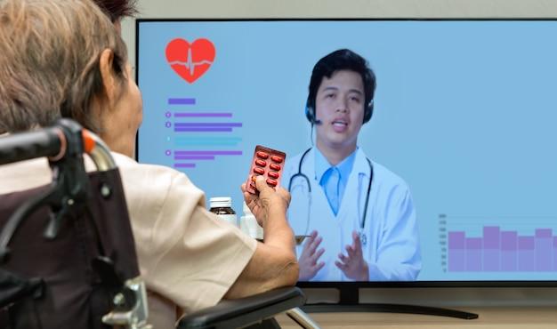 노인 여성은 태블릿 컴퓨터로 의사와 온라인 상담을 하며 집에 앉아 있습니다.