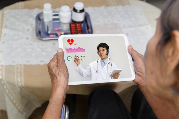 高齢者の女性は、タブレットコンピューターで医師とオンライン相談を持つ自宅で座っています。