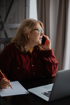 Elderly woman sits at the computer and talking  by phone