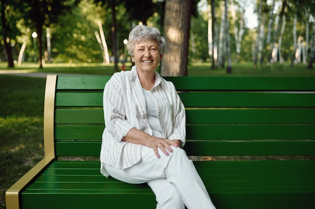 An elderly woman sitting on the bench in summer park. aged people lifestyle. pretty grandmother having fun outdoors, old female person on nature