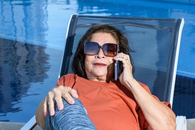 電話で話しているプールのそばに座っている年配の女性