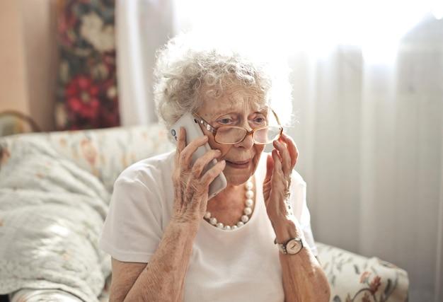 그녀의 얼굴에 걱정 표정으로 전화에 앉아있는 노인 여성