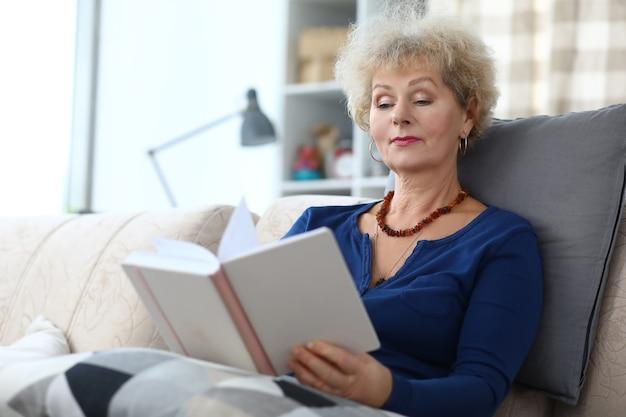 Пожилая женщина сидит на диване и читает книгу дома