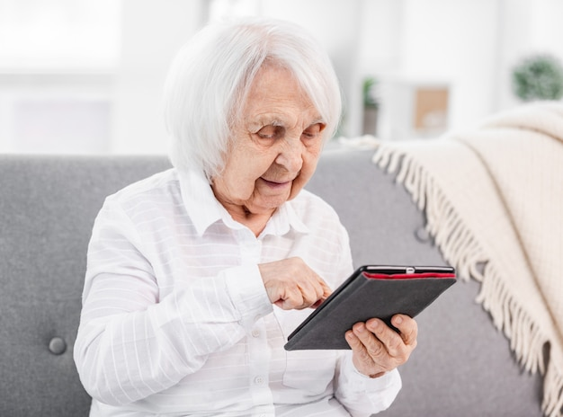 Elderly woman sitting with tablet on the sofa and looking at the screen