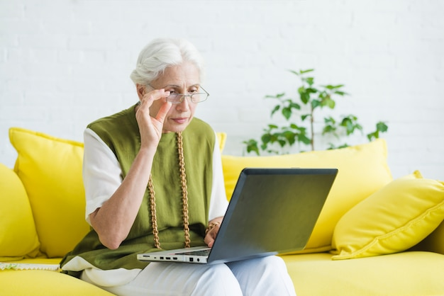 An elderly woman sitting on yellow sofa looking at laptop