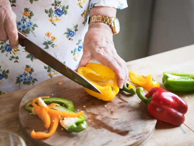 Elderly woman slicing bell peppers