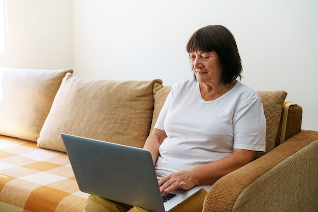 Пожилая женщина улыбается s, сидя дома на диване, держа ноутбук старший счастливая деловая женщина, использующая ко ...