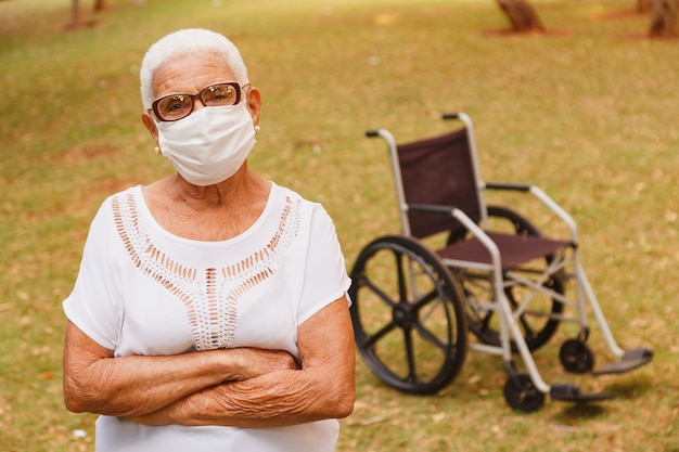 교차 팔으로 covid에 대한 보호 마스크와 함께 웃 고 노인 여성