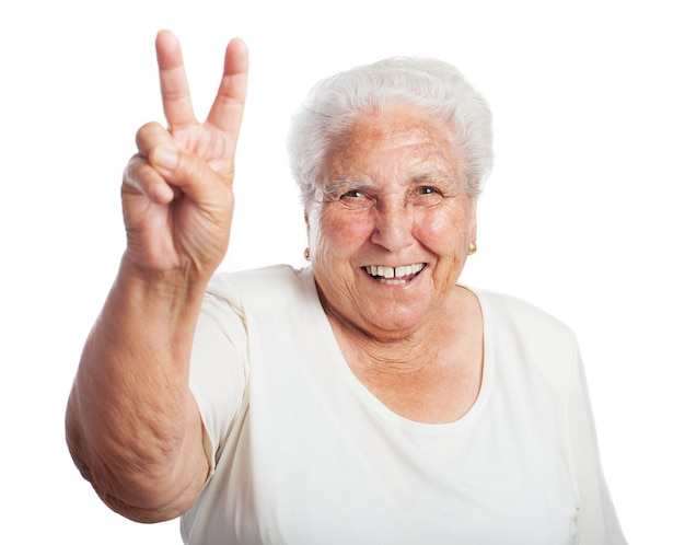 Elderly woman smiling with two raised fingers
