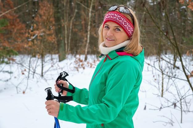 겨울 숲에서 노르딕 워킹 폴 서 노인 여성