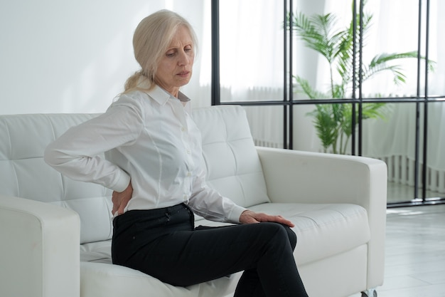 An elderly woman suffering from back pain a middleaged woman gets up from the sofa and experiences back pain