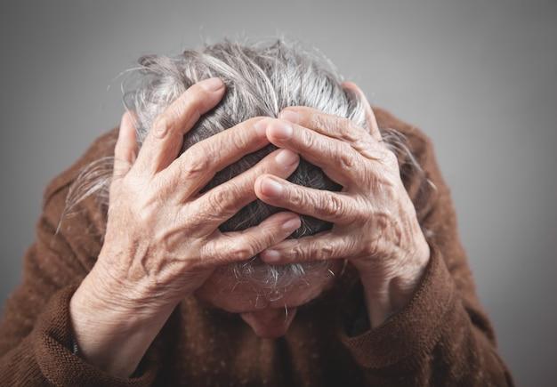 Пожилая женщина страдает головной болью.