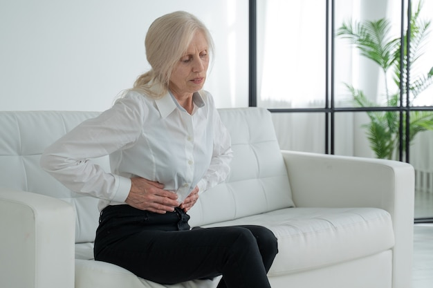 An elderly woman suffers from abdominal pain a mature elderly adult woman feels abdominal pain while sitting on the couch