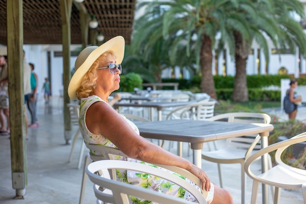 Elderly woman in sunglasses and a hat sits alone at a table in a summer cafe
