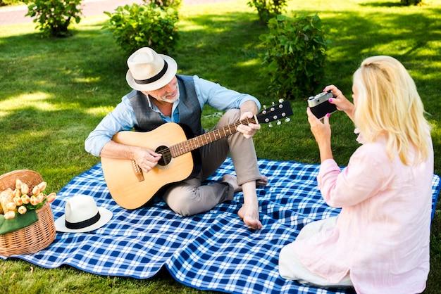 Пожилая женщина фотографирует на пикнике