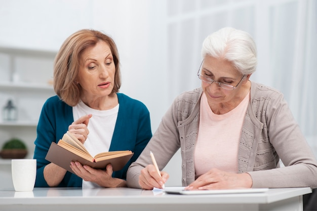 Elderly woman taking notes together