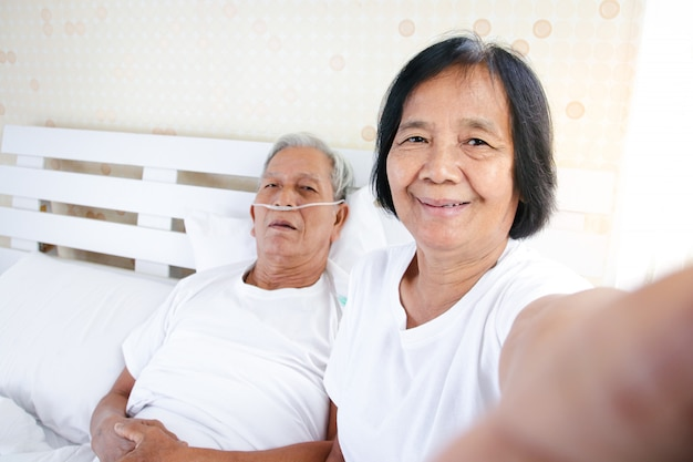 An elderly woman taking a picture with her husband who is suffering from lung disease and respiratory disease in bed in the bedroom. concept of care, encouragement and prevention of coronavirus
