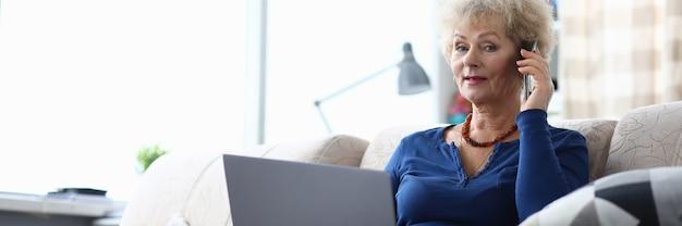 Пожилая женщина разговаривает по смартфону и держит ноутбук, сидя на диване