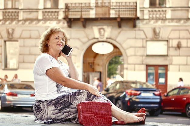 Пожилая женщина разговаривает по телефону во время прогулки по центру города