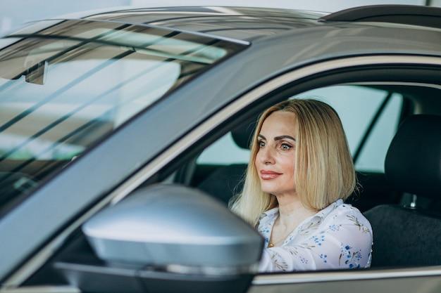 Elderly woman testing a car in car showroom