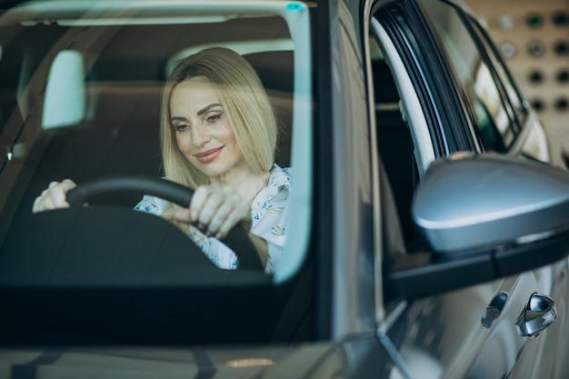 Donna anziana che collauda un'automobile nella sala d'esposizione dell'automobile