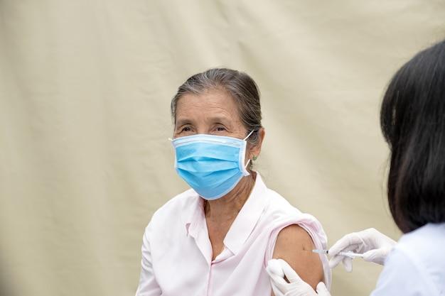 Пожилая женщина, рука врача держала шприц и собиралась вакцинировать пациента в клинике, чтобы предотвратить распространение вируса