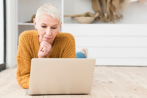 Elderly woman thinking and looking at laptop