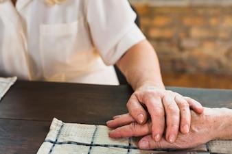 Elderly woman touching hand of husband