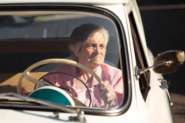 白い車で旅行する年配の女性