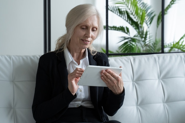 Пожилая женщина использует цифровой планшет, сидя на диване дома, использование технологий пожилыми людьми
