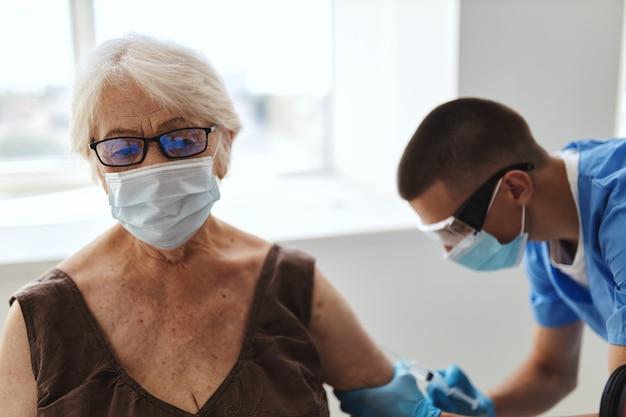 病院での高齢女性のワクチン接種コロナウイルスパンデミックコビッド