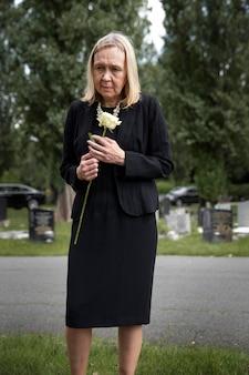 Donna anziana che visita la tomba della persona amata