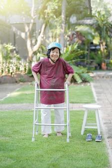 Elderly woman walking barefoot therapy on grass in backyard.