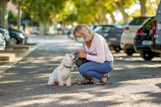 Пожилая женщина гуляет с собакой на открытом воздухе в антивирусной маске.