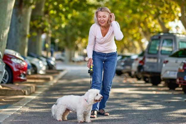 야외에서 강아지와 함께 산책하는 노인 여성