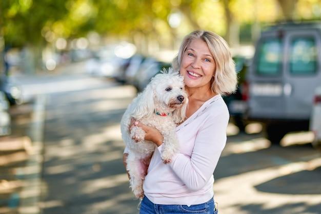 Пожилая женщина гуляет с собакой на открытом воздухе.